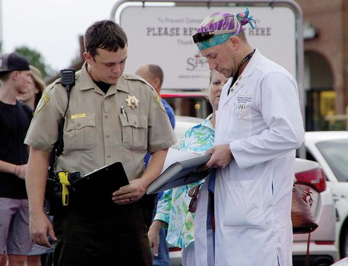 Dave Crittenden, who was the first to help the victim, speaks to a deputy about the incident