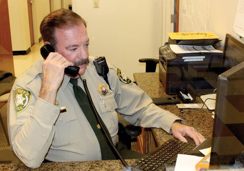 Deputy Jon Beival takes a call from a resident