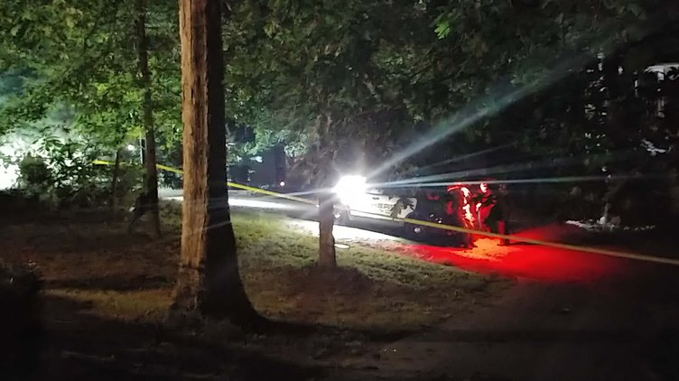 Crime scene tape winds through the trees